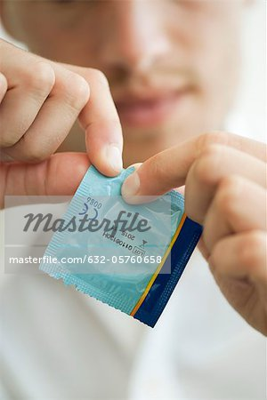 Man opening condom wrapper, cropped Stock Photo - Premium Royalty-Free, Image code: 632-05760658