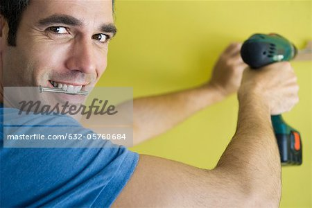 Man using power drill, biting screw in mouth Stock Photo - Premium Royalty-Free, Image code: 632-05760684