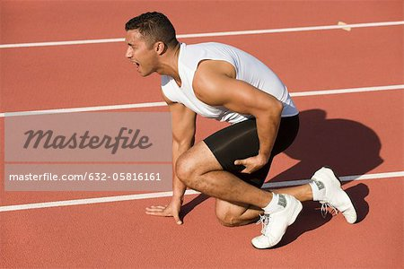 Injured runner kneeling on running track Stock Photo - Premium Royalty-Free, Image code: 632-05816161