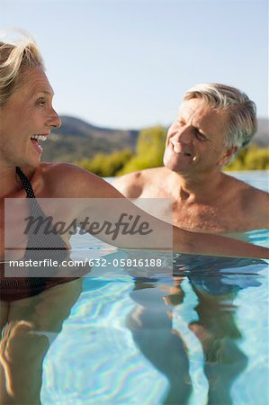 Mature couple relaxing together in pool Stock Photo - Premium Royalty-Free, Image code: 632-05816188