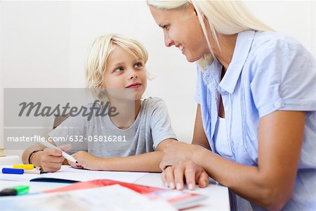 Mother helping son with homework Stock Photo - Premium Royalty-Free, Image code: 632-05816281