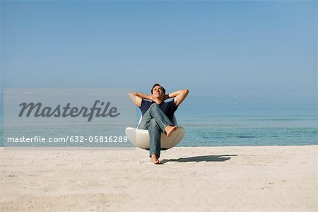 Mid-adult man relaxing in armchair on beach with eyes closed Stock Photo - Premium Royalty-Free, Image code: 632-05816289