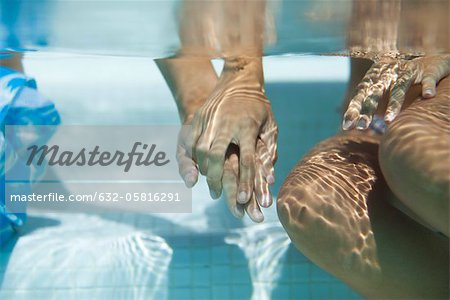 Couple holding hands underwater, cropped Stock Photo - Premium Royalty-Free, Image code: 632-05816291