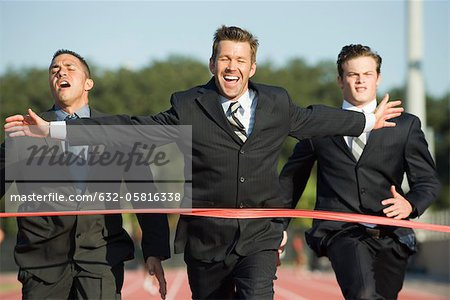 Businessman crossing finish line in race Stock Photo - Premium Royalty-Free, Image code: 632-05816338