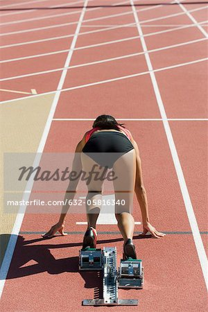Woman crouched in starting position on running track, rear view Stock Photo - Premium Royalty-Free, Image code: 632-05816340