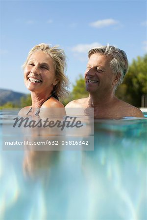 Mature couple relaxing together in pool Stock Photo - Premium Royalty-Free, Image code: 632-05816342