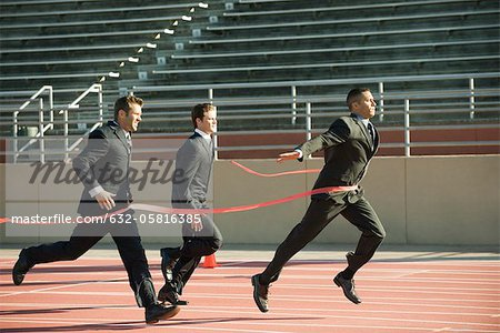 Businessman crossing finish line in race Stock Photo - Premium Royalty-Free, Image code: 632-05816385