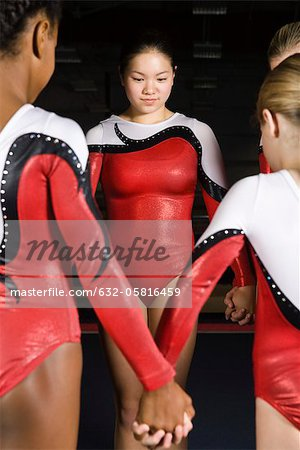 Team of gymnasts holding hands Stock Photo - Premium Royalty-Free, Image code: 632-05816459