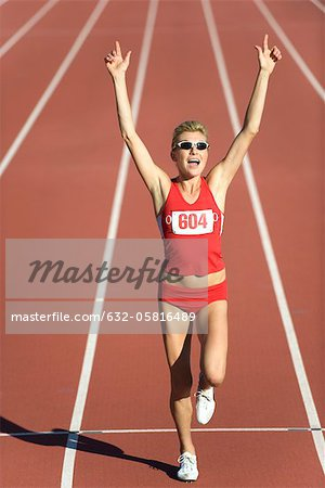 Woman running on track with arms raised in victory Stock Photo - Premium Royalty-Free, Image code: 632-05816489