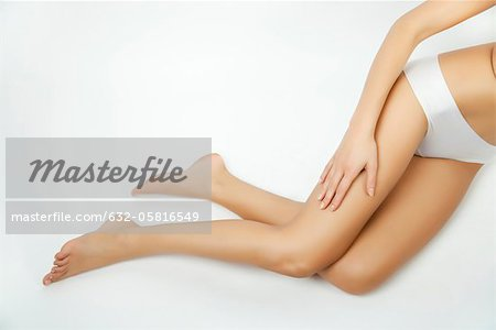 Woman touching her bare leg, cropped Stock Photo - Premium Royalty-Free, Image code: 632-05816549
