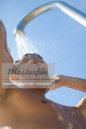 Man using outdoor shower Stock Photo - Premium Royalty-Free, Image code: 632-05816619