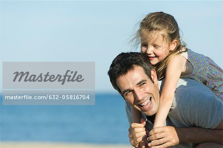 Father giving young daughter piggyback ride Stock Photo - Premium Royalty-Free, Image code: 632-05816704