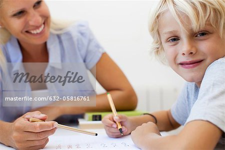 Boy doing homework, smiling at camera Stock Photo - Premium Royalty-Free, Image code: 632-05816761