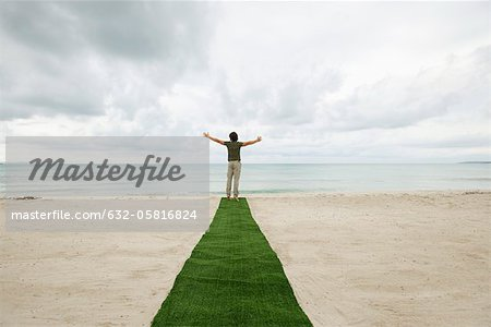 Man standing at end of carpet on beach with arms outstretched, rear view Stock Photo - Premium Royalty-Free, Image code: 632-05816824