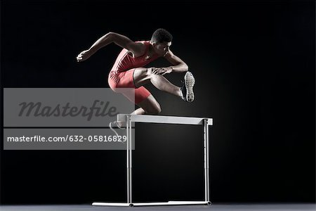Male athlete clearing hurdle Stock Photo - Premium Royalty-Free, Image code: 632-05816829