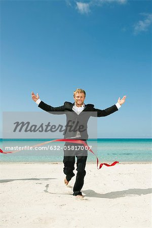 Young businessman running on beach towards finishing line Stock Photo - Premium Royalty-Free, Image code: 632-05817007