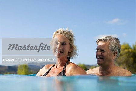 Mature couple relaxing together in pool Stock Photo - Premium Royalty-Free, Image code: 632-05817023