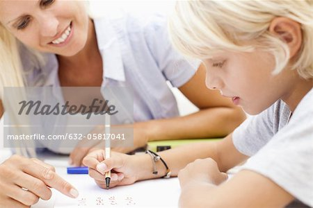 Mother helping son with homework Stock Photo - Premium Royalty-Free, Image code: 632-05817041