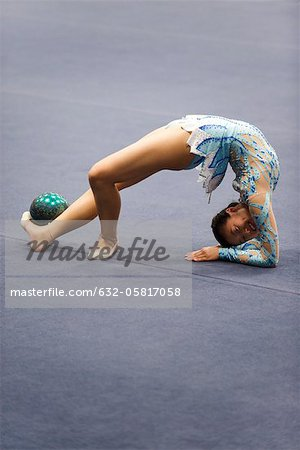 Female gymnast performing floor routine with ball Stock Photo - Premium Royalty-Free, Image code: 632-05817058