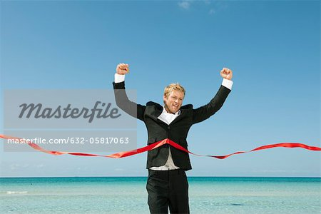 Young businessman crossing finishing line Stock Photo - Premium Royalty-Free, Image code: 632-05817063