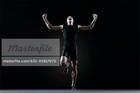 Male athlete flexing arms and shouting Stock Photo - Premium Royalty-Free, Image code: 632-05817072