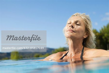 Mature woman relaxing in pool with eyes closed Stock Photo - Premium Royalty-Free, Image code: 632-05817089