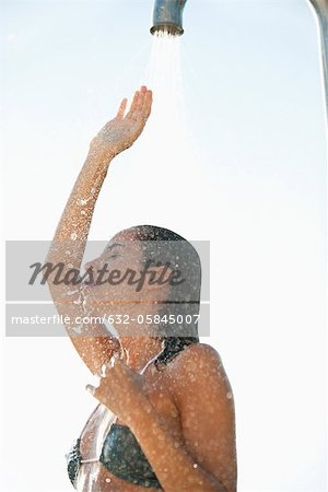 Mid-adult woman enjoying shower outdoors Stock Photo - Premium Royalty-Free, Image code: 632-05845007