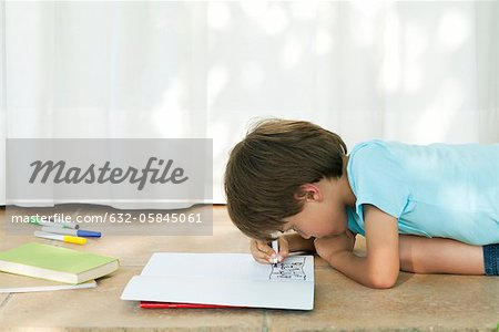Boy drawing in notebook Stock Photo - Premium Royalty-Free, Image code: 632-05845061