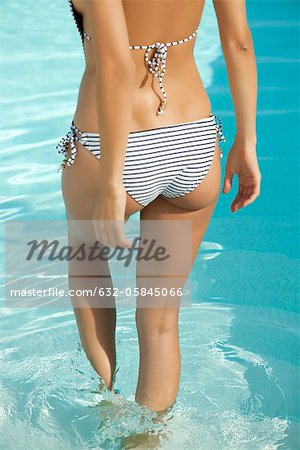 Woman wading in swimming pool, cropped rear view Stock Photo - Premium Royalty-Free, Image code: 632-05845066