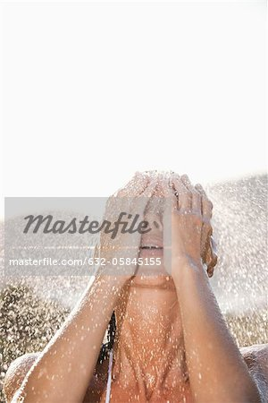Woman washing face under shower outdoors Stock Photo - Premium Royalty-Free, Image code: 632-05845155