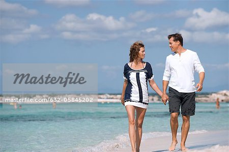 Couple walking on beach holding hands, portrait Stock Photo - Premium Royalty-Free, Image code: 632-05845202