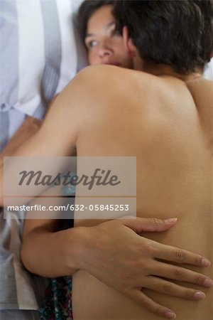 Naked young couple embracing in bed Stock Photo - Premium Royalty-Free, Image code: 632-05845253