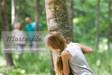 Girl hiking behind tree in woods Stock Photo - Premium Royalty-Free, Image code: 632-05845359