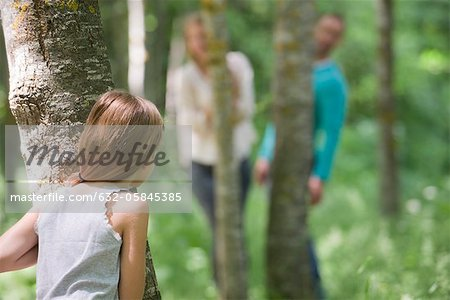 Girl playing hide and seek with parents in woods, rear view Stock Photo - Premium Royalty-Free, Image code: 632-05845385