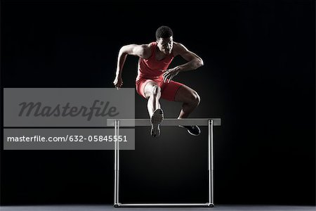 Male athlete clearing hurdle Stock Photo - Premium Royalty-Free, Image code: 632-05845551
