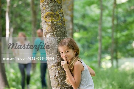 Girl hiding behind tree with finger on lips Stock Photo - Premium Royalty-Free, Image code: 632-05845584