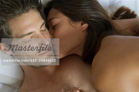 Naked couple kissing in bed, high angle view Stock Photo - Premium Royalty-Free, Image code: 632-05845612