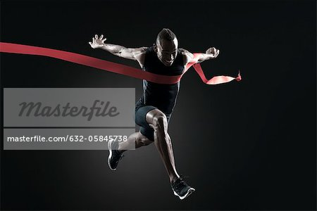Runner crossing finish line Stock Photo - Premium Royalty-Free, Image code: 632-05845738