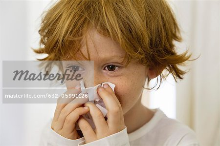 Boy blowing nose on tissue Stock Photo - Premium Royalty-Free, Image code: 632-05991126