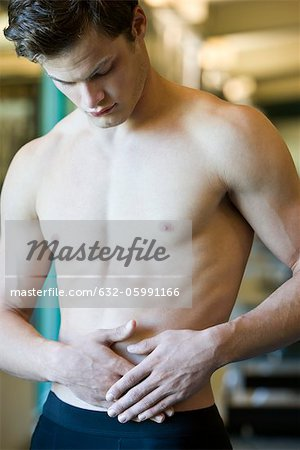 Barechested young man with hands on stomach Stock Photo - Premium Royalty-Free, Image code: 632-05991166