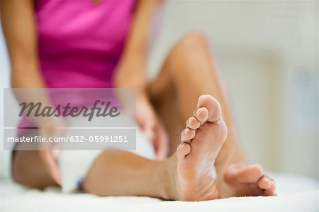 Woman sitting with ice pack on knee, focus on foreground Stock Photo - Premium Royalty-Free, Image code: 632-05991251