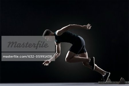 Runner leaving starting block Stock Photo - Premium Royalty-Free, Image code: 632-05991438
