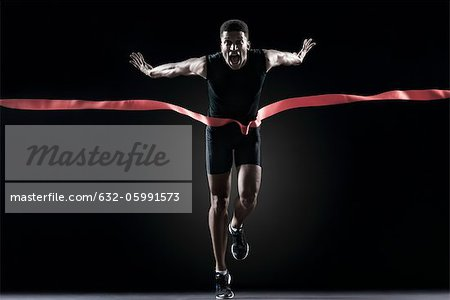 Runner crossing finishing line Stock Photo - Premium Royalty-Free, Image code: 632-05991573