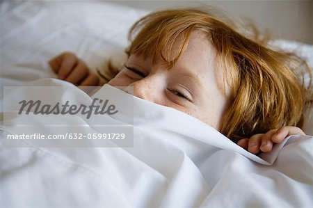 Boy lying in bed with bed sheet covering face Stock Photo - Premium Royalty-Free, Image code: 632-05991729