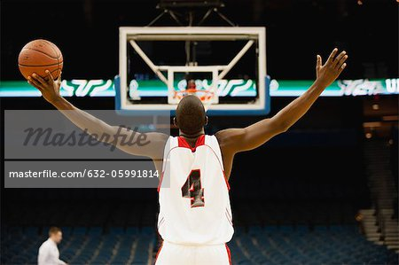 Basketball player standing in basketball court with arms outstretched, rear view Stock Photo - Premium Royalty-Free, Image code: 632-05991814