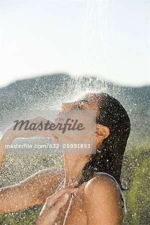 Mid-adult woman showering outdoors Stock Photo - Premium Royalty-Free, Image code: 632-05991893