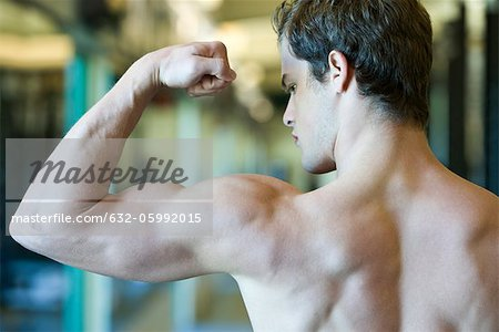 Young man flexing bicep muscles Stock Photo - Premium Royalty-Free, Image code: 632-05992015
