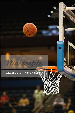 Basketball in midair above basketball hoop Stock Photo - Premium Royalty-Free, Image code: 632-05992101