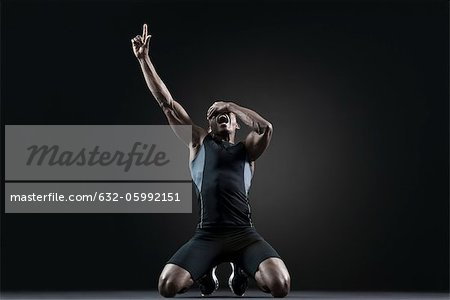 Male athlete shouting with finger pointing up Stock Photo - Premium Royalty-Free, Image code: 632-05992151
