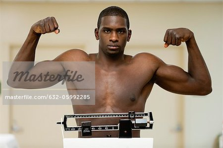Young man flexing muscle on weight scale, portrait Stock Photo - Premium Royalty-Free, Image code: 632-05992285